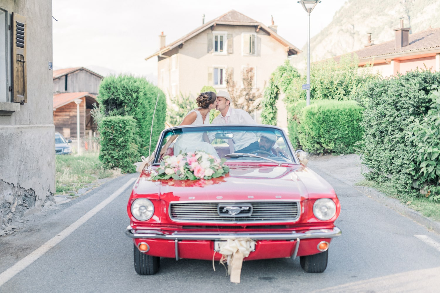The newlyweds in a red Ford Mustang