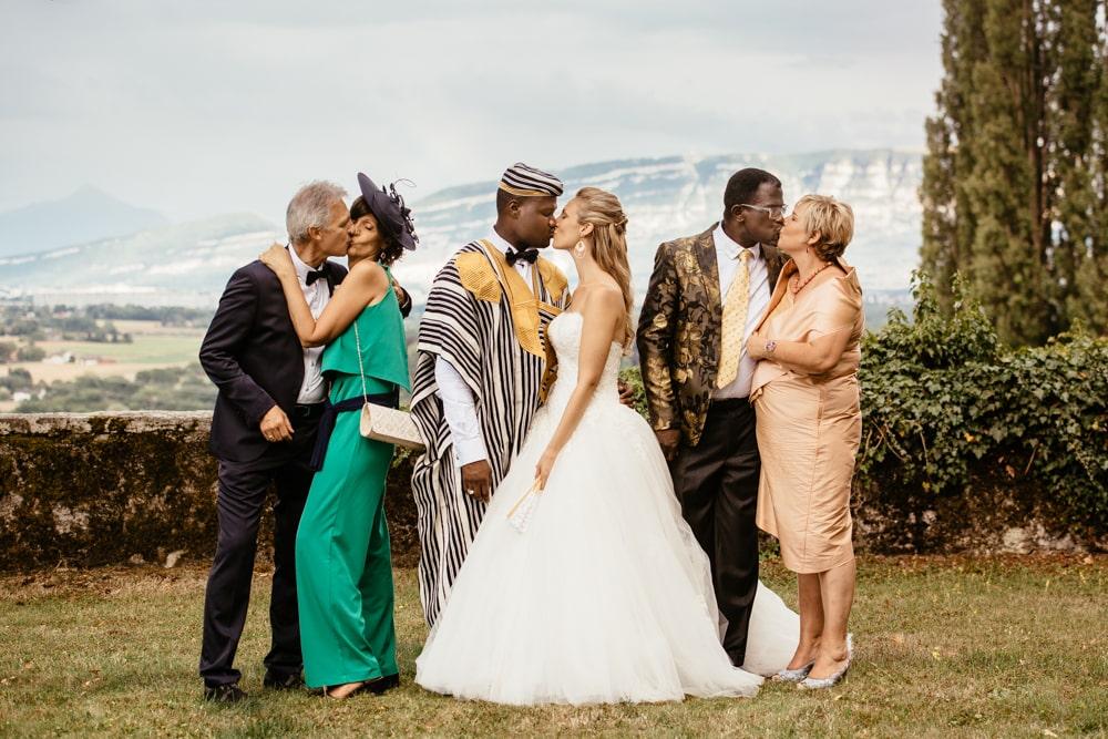Les mariés s'embrassent, entourés de leurs familles