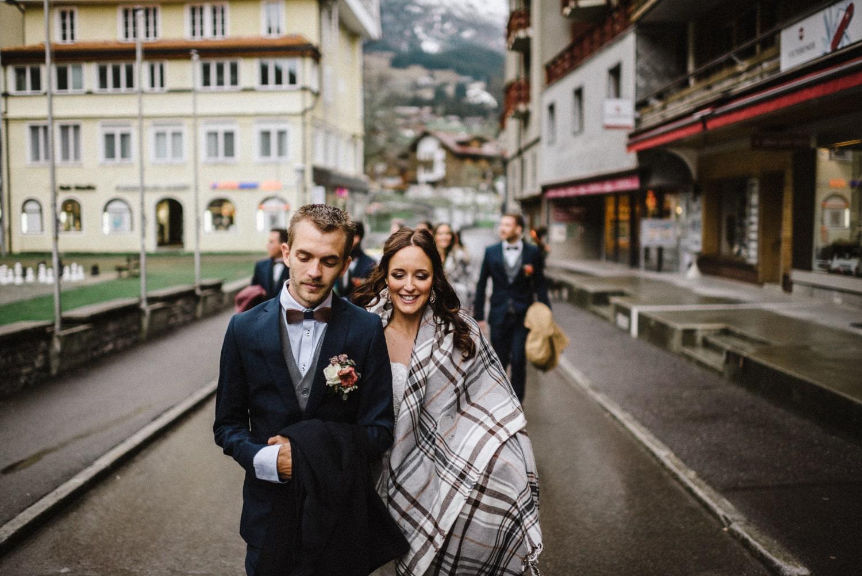 Couple de mariés heureux marchant sous la pluie
