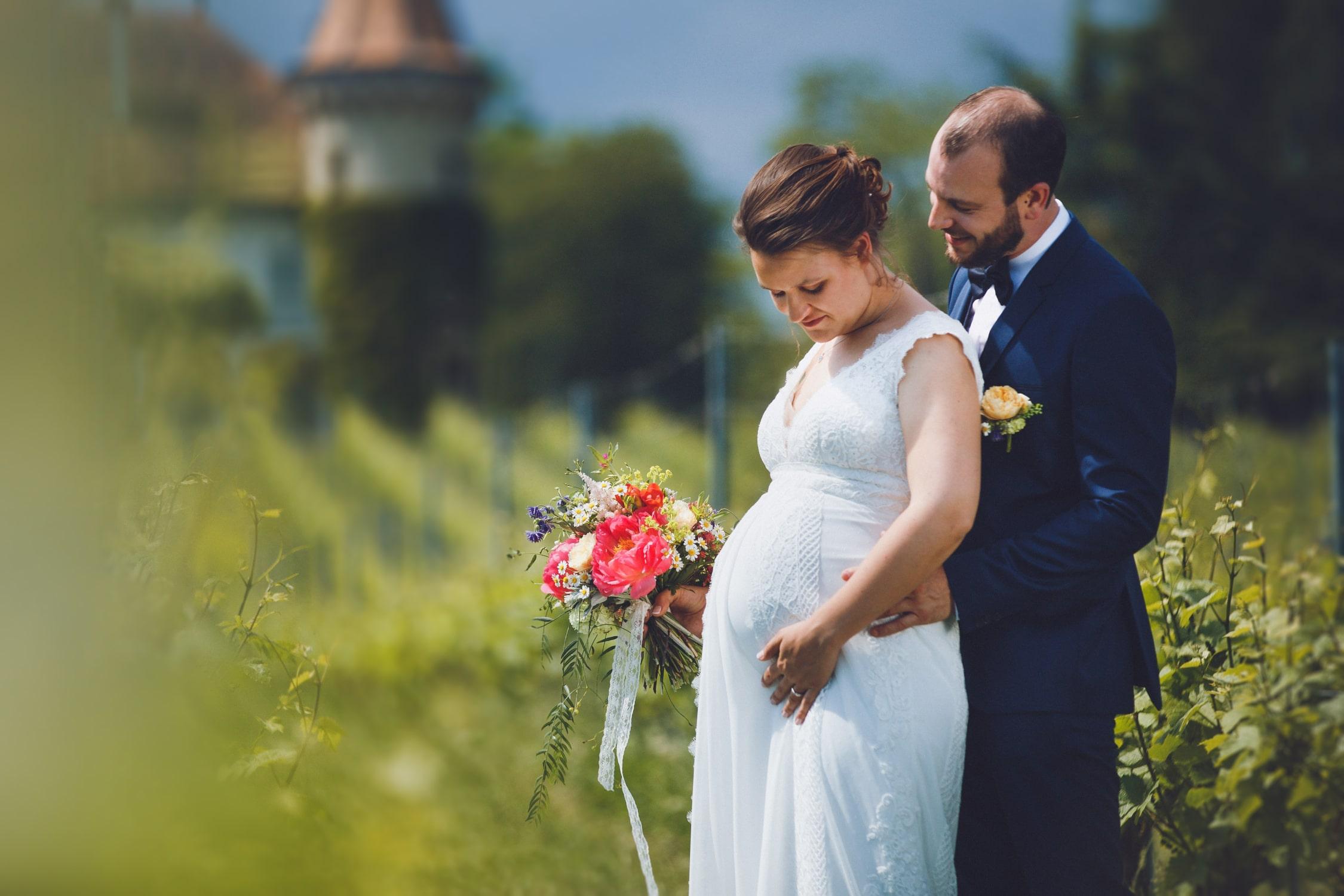 couple de futurs parents posant dans un vignoble suisse