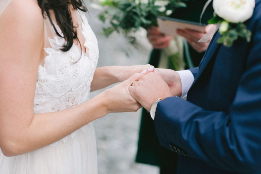 Bride and groom holding hands during their intimate wedding ceremony