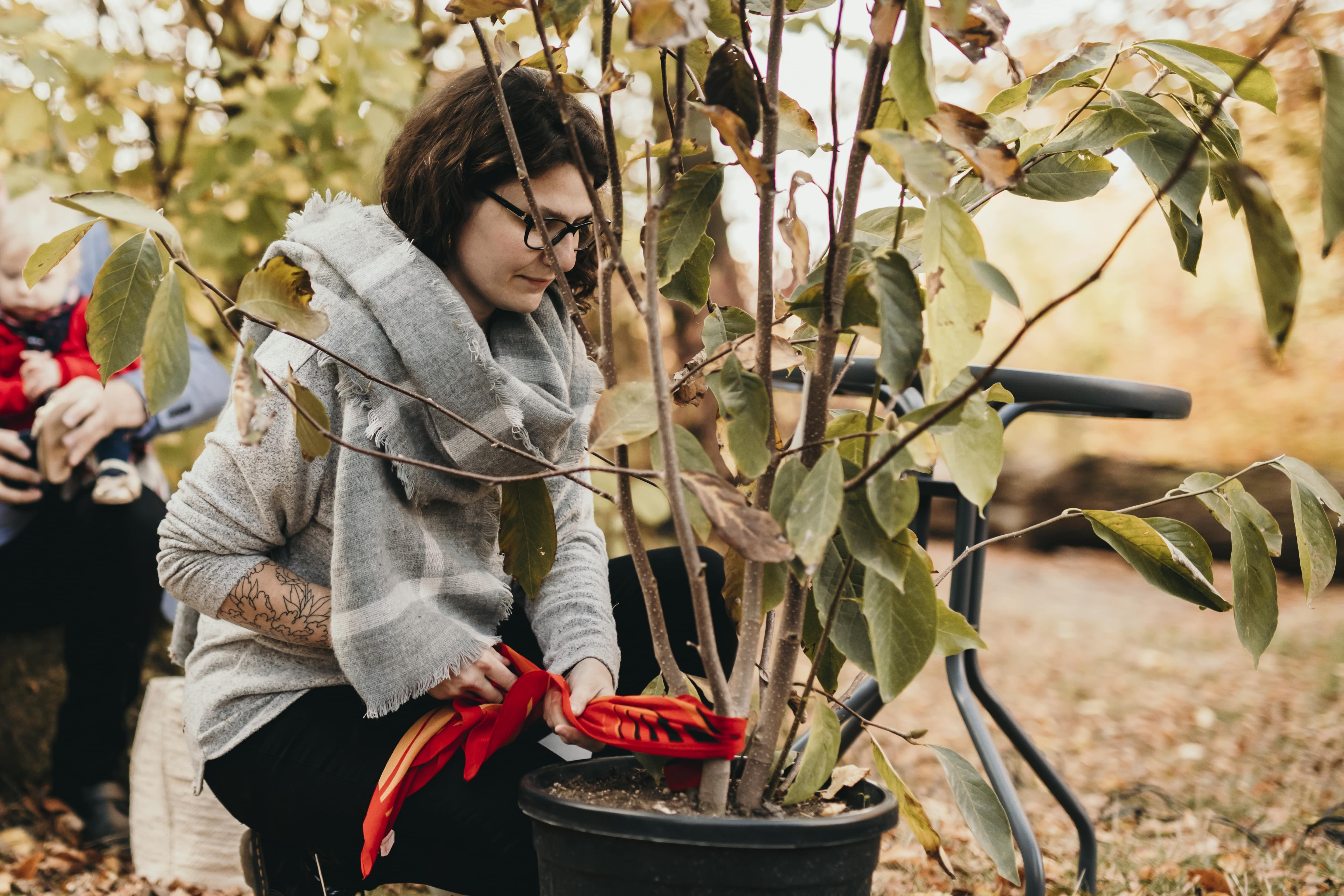 La maman accroche un foulard à l'arbre symbolique