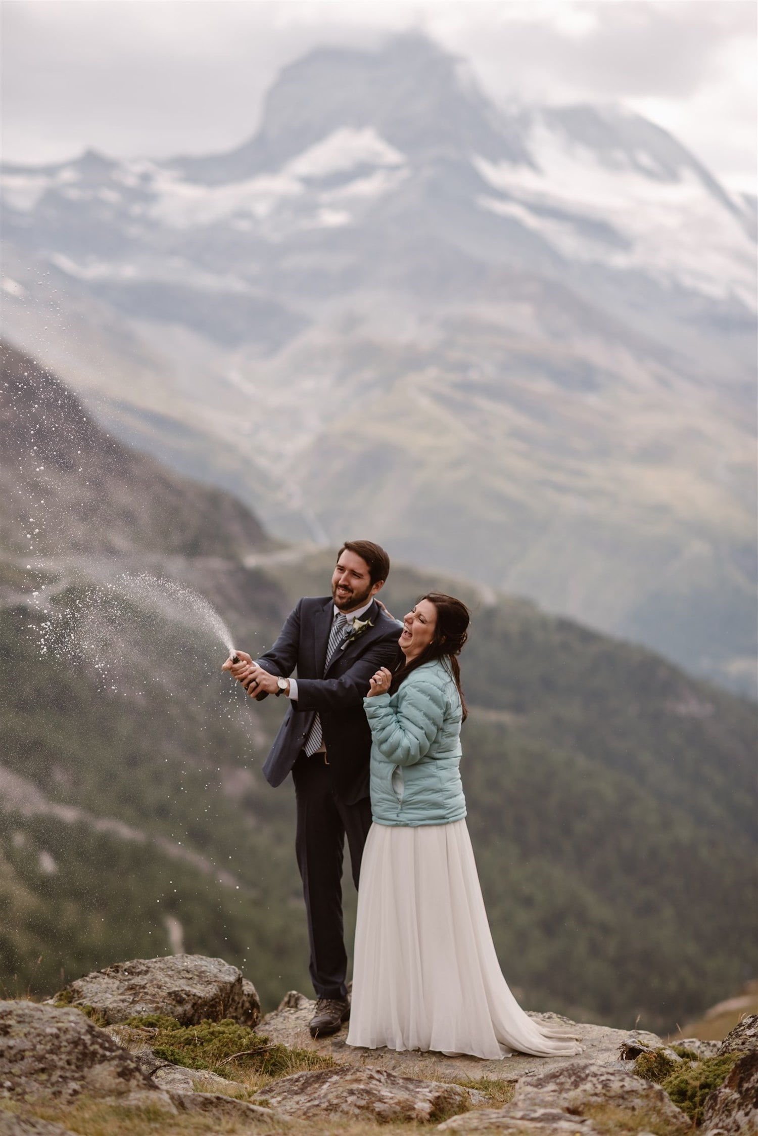 Newlyweds popping the Champagne during their summer elopement in Zermatt